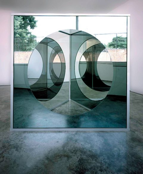 GRAD010001 Dan Graham,'Triangular Pavilion with Circular Cut-Out Variation C', 1989~2001,Two Way Mirror Glass, Plain Glass, Painted Aluminium and Stainless Steel205×208cm80.7×81.9in© Dan Graham; Courtesy Lisson Gallery