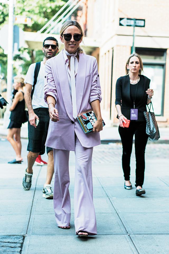 오버사이즈의 핑크 수트에 키치한 클러치 백을 매치했다.