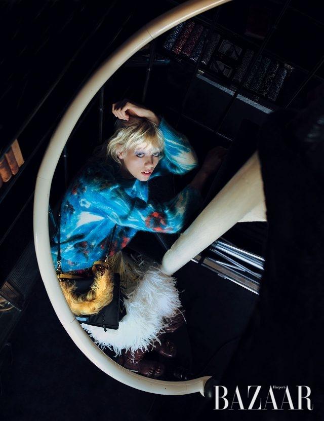 플라워 모티프의 모헤어 니트, 헴라인에 깃털을 장식한 스커트, 테스토 에티켓 백, 퍼 소재의 핸들 장식, 버클 디테일의 사이하이 부츠는 모두 Prada 제품.