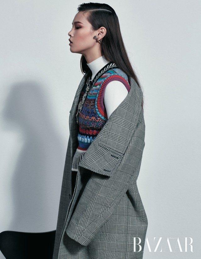 클래식한 글렌체크 코트와 링 디테일 터틀넥 니트는 모두 Stella McCartney, 포크 무드의 니트 베스트, 브로치처럼 연출한 오버사이즈 귀고리는 모두 Burberry, 로즈 모티프의 귀고리는 Saint Laurent by Anthony Vaccarello 제품.