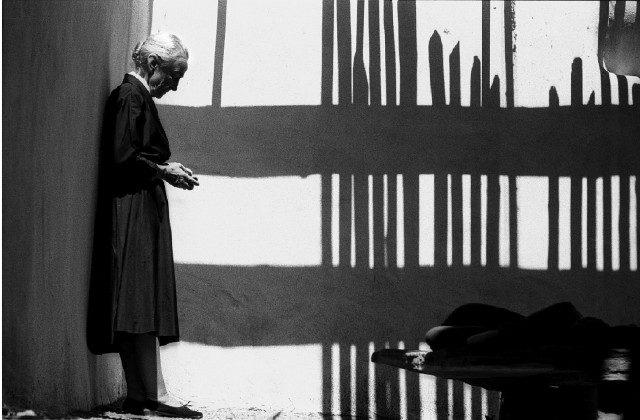 애비퀴우 하우스의 뜰, 펜스의 그림자가 진 벽에 기대어 서 있는 오키프, 1966.photo: John oengard / Time & Life Pictures / Getty Images