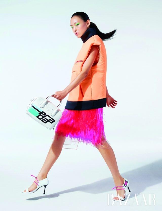패딩 베스트, PVC 프린지 스커트, 함께 레이어링한 오간자 시스루 드레스, 새롭게 선보인 그래픽 로고가 프린트된 토트백, 고무 스트링 장식 스트랩 힐은 모두 가격 미정으로 Prada 제품.