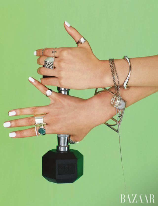 왼손에 착용한 유선형 팔찌는 1백71만원 Charlotte Chesnais by Mue, 팔찌로 연출한 목걸이는 69만원, 왼손 엄지에 착용한 반지는 53만원 모두 Maison Margiela, 목걸이에 연결한 십자가 펜던트, 검지에 착용한 반지들은 모두 Chrome Hearts, 중지에 착용한 반지는 Celine by Hedi Slimane, 오른손에 착용한 팔찌, 중지에 낀 반지는 모두 Hermès, 오른손 엄지에 착용한 반지는 57만원 Bottega Veneta, 검지에 착용한 원석 세팅 반지는 59만원, 소지에 착용한 반지는 57만원 모두 Tom Wood by BOONTHESHOP, 검지에 낀 크리스털 장식 반지는 10만원 Bittersweet, 덤벨은 1만원대 Batu Sports.