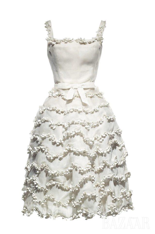 은방울 꽃 모티프를 장식한 화이트 오간디 소재의 쇼트 이브닝 드레스 '뮤게(Muguet)'. 1957 S/S 오트 쿠튀르, 리브레(Libre) 라인. 디올 헤리티지 컬렉션. 프란신 바이스바일러 (Francine Weisweiller)가 착용했다.