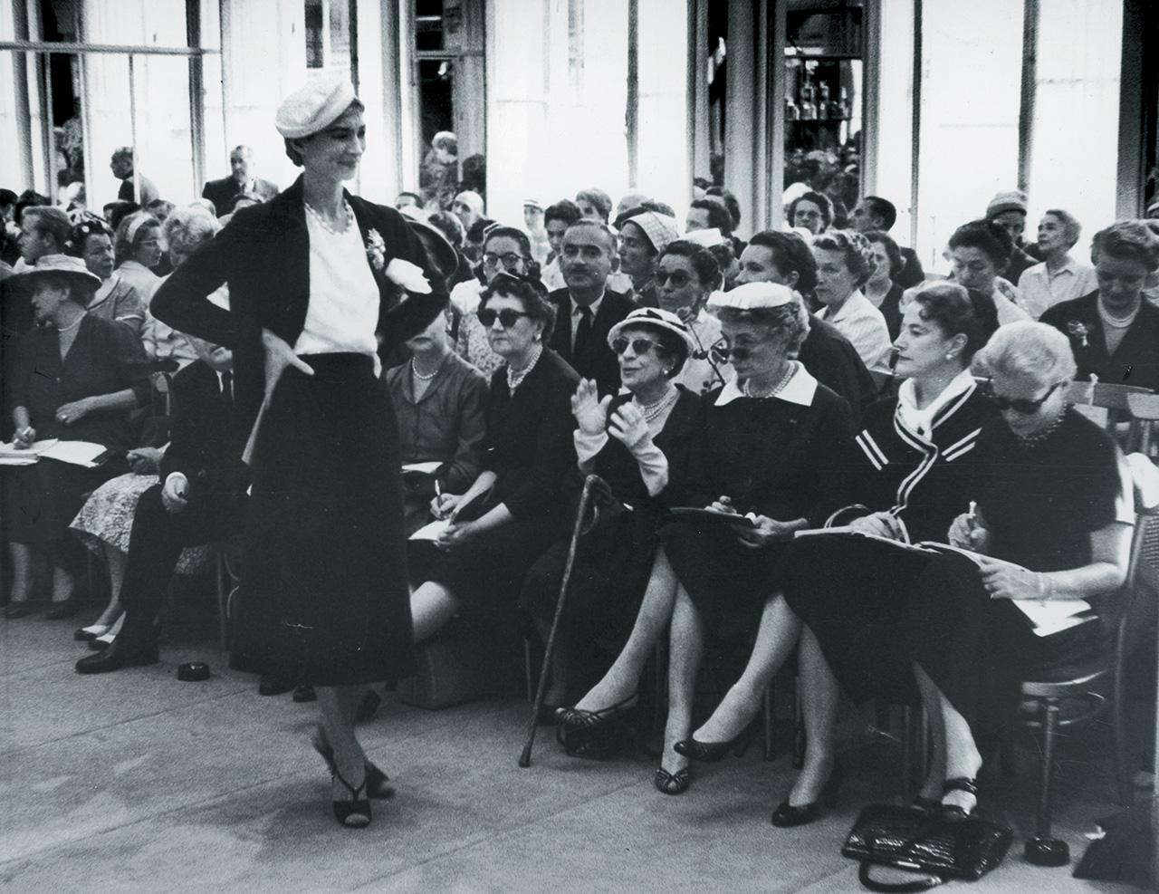 1955년 파리에서 열린 디올 쇼. 선글라스 너머로 쇼를 바라보고 있는 카멜 스노