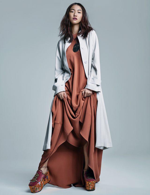 미니멀한 트렌치코트는 Bottega Veneta, 플레어 롱 드레스는 Valentino, 얼굴 모티프의 펜던트 목걸이는 63만원으로 J.W Anderson by BOONTHESHOP, 자수 장식의 자카드 통굽 슈즈는 Gucci 제품.