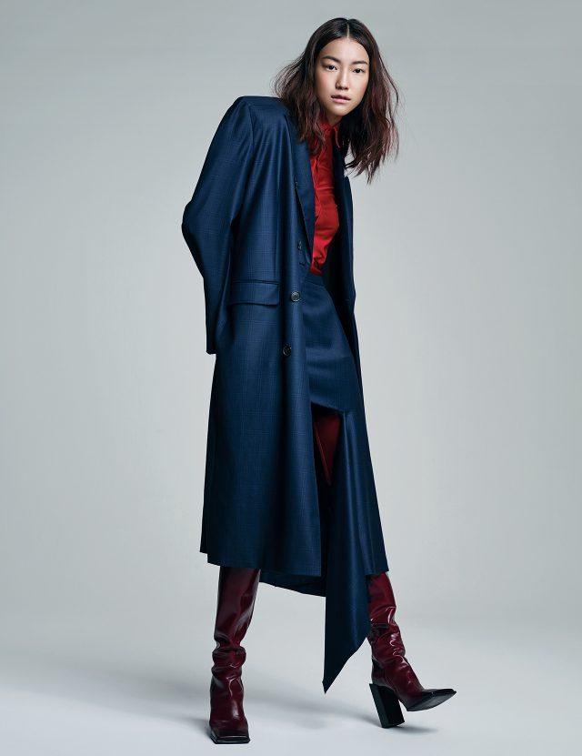 과장된 어깨의 힘. 어깨가 강조된 코트, 저지 버튼업 셔츠, 비대칭 컷아웃 스커트, 사이하이 부츠는 모두 Balenciaga 제품.