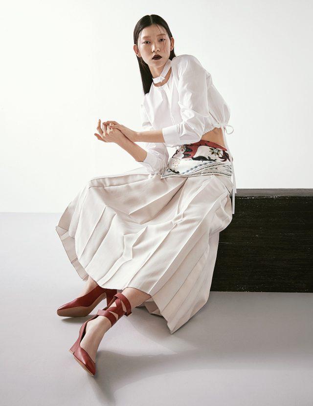 칼라가 컷아웃된 크롭트 셔츠는 99만원으로 Alexander Wang by BOONTHESHOP, 플리츠 스커트는 Bottega Veneta, 허리에 두른 실크 스카프는 Dior, 레이스업 슈즈는 Valentino Garavani 제품.