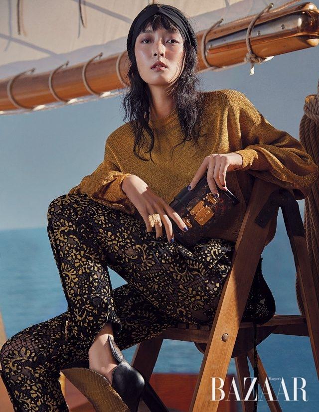 골드 니트 스웨터, 레이스 팬츠, 메탈릭 부츠, 트렁크 형태의 미니 클러치 백은 모두 Louis Vuitton 제품.