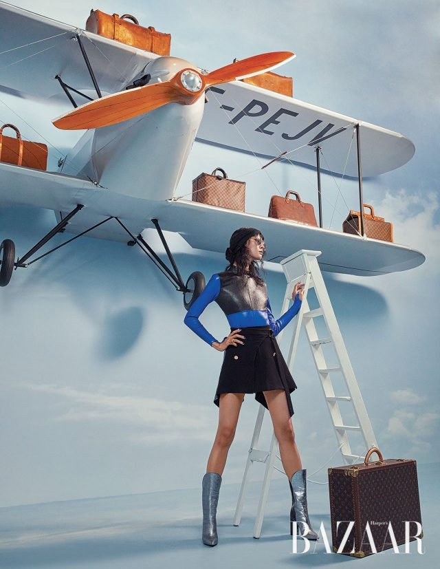가죽 보디수트, 버튼업 랩 스커트, 투 톤 선글라스, 메탈릭 부츠, 클래식 트렁크 화보에서 계속 착용하고 있는 헤드밴드와 반지는 모두 Louis Vuitton 제품.