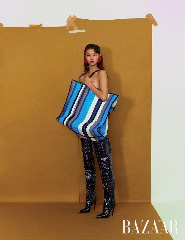 스트라이프 패턴의 오버사이즈 '바자' 백, 로고 사이하이 부츠, 화보에서 계속 착용하고 있는 퍼 귀고리는 모두 Balenciaga 제품.