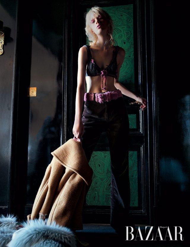 레트로 무드의 니트 브라 톱, 코듀로이 소재 벨보텀 팬츠, 손에 들고 연출한 퍼 장식의 알파카 코트, 송치 소재 벨트, 퍼 슬라이드는 모두 Prada 제품.