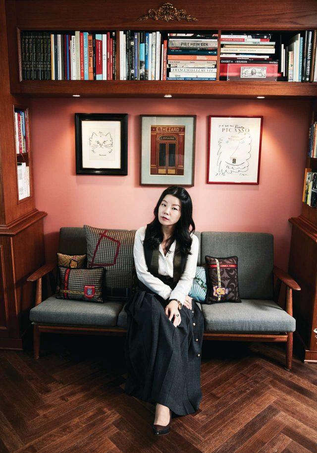 자크 브랑주의 서재 사진에서 영감을 얻어 만든 'ᄃ' 자형 책장 사이의 한스 베그너 소파에 앉은 딜런 류.