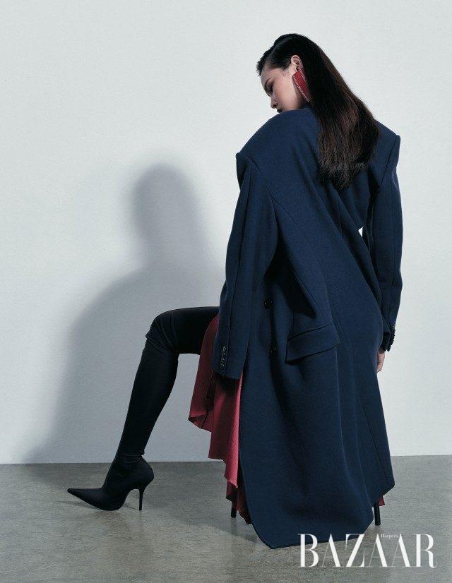 어깨가 강조된 구조적인 오버사이즈 코트, 유연한 실크 드레스, 볼드한 귀고리, 과감한 매력의 사이하이 부츠는 모두 Balenciaga 제품.