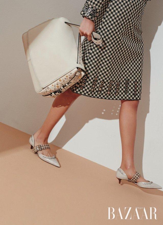 깅엄체크 패턴과 메탈 아일릿 디테일이 조화로운 재킷은 200만원대, 펜슬 스커트는 200만원대, 아일릿 디테일을 가미한 백은 600만원대, 벨티드 디테일의 키튼 힐은 100만원대로 모두 Bottega Veneta 제품.