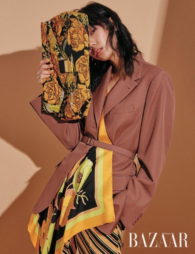 스카프 디테일을 덧댄 재킷, 스트라이프 팬츠, 꽃 자수가 놓인 클러치는 모두 가격 미정으로 Dries Van Noten 제품.