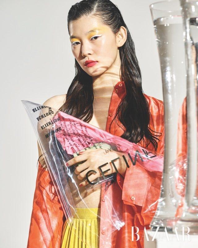 실키한 소재의 오버사이즈 셔츠는 가격 미정으로 Hermès, 플리츠 스커트는 65만원으로 Enföld by BOONTHESHOP, 비비드한 컬러의 지갑과 함께 드는 투명한 비닐 소재의 쇼퍼 백은 가격 미정으로 Céline 제품.