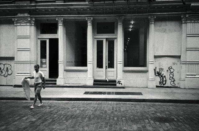 데이비드 즈워너가 갤러리 앞에서 제이슨 로즈의 개인전 의 사인을 들고 있다. 1993.