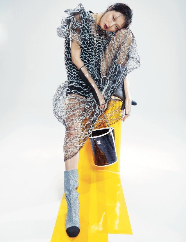 로고와 카멜리아 모티프가 프린팅된 버킷 백, 블랙 앤 화이트의 니팅 드레스, 장갑, 두 개를 레이어드한 목걸이, 글리터링 소재의 부츠는 모두 Chanel 제품.