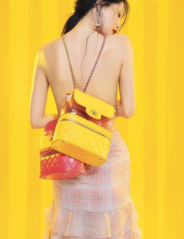 글로시한 소재와 퀼팅 디테일이 돋보이는 옐로, 핑크 컬러의 숄더 겸용 백팩, 러플 장식 롱스커트, 로고 장식 귀고리는 모두 Chanel 제품.