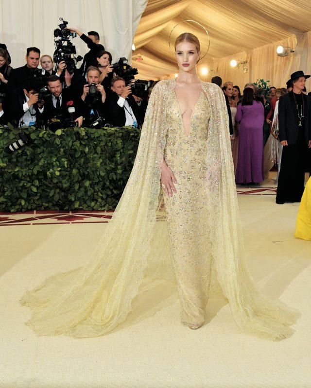 로지 헌팅턴 휘틀리는 랄프 로렌의 우아한 골드 케이프 드레스와 성스러움을 상징하는 헤드 피스로 영광의 성모마리아를 재현했다.