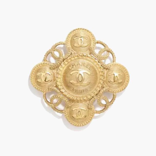 빈티지한 메탈 브로치는 Chanel 제품.