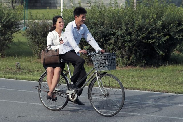 커플 룩으로 맞춰입고 자전거를 함께 타는 연인들.