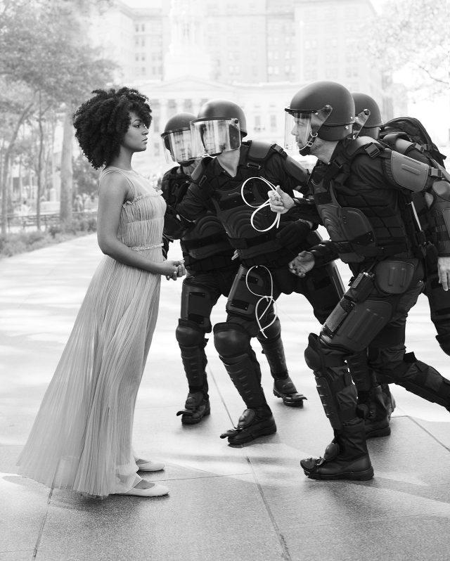 에반스가 그녀의 체포 순간을 재현하고 있다. 드레스와 슈즈는 Dior.