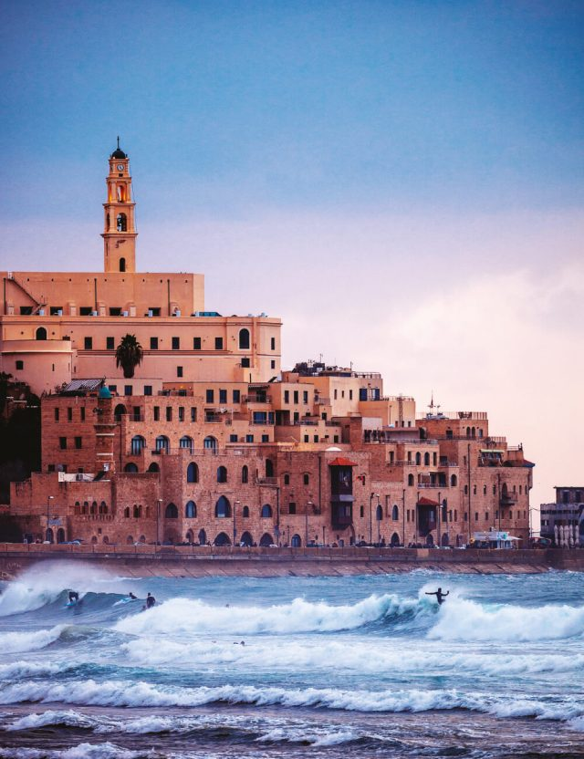 이스라엘 텔아비브의 남쪽에 위치한 지중해안 항구도시 자파에서 석양을 받으며 서핑하는 서퍼들의 모습.